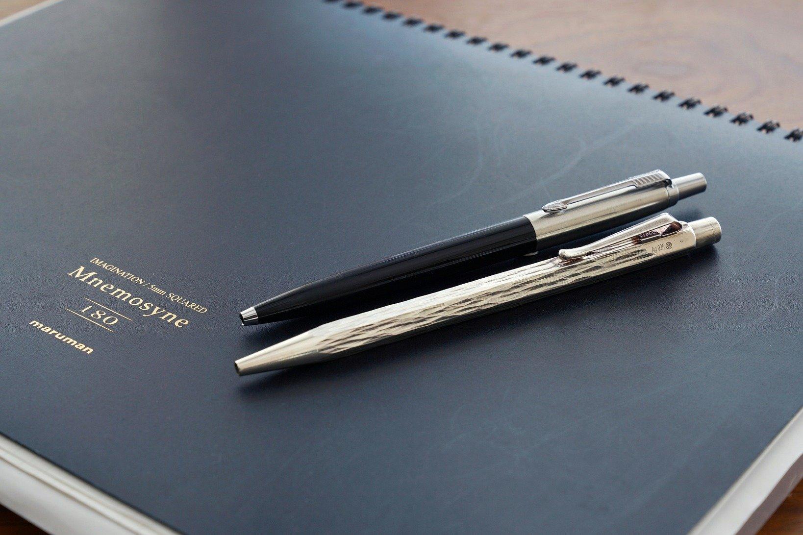 飯野さんお気に入りのノートと、万年筆が使えない環境で出番となるパーカーのボールペン「ジョッター」(左)とカランダッシュのエクリドール スターリングシルバー ベネシアン(右)。因みにこのパーカーは1970年代製。つまり小学生の頃からずっと使っているもの。