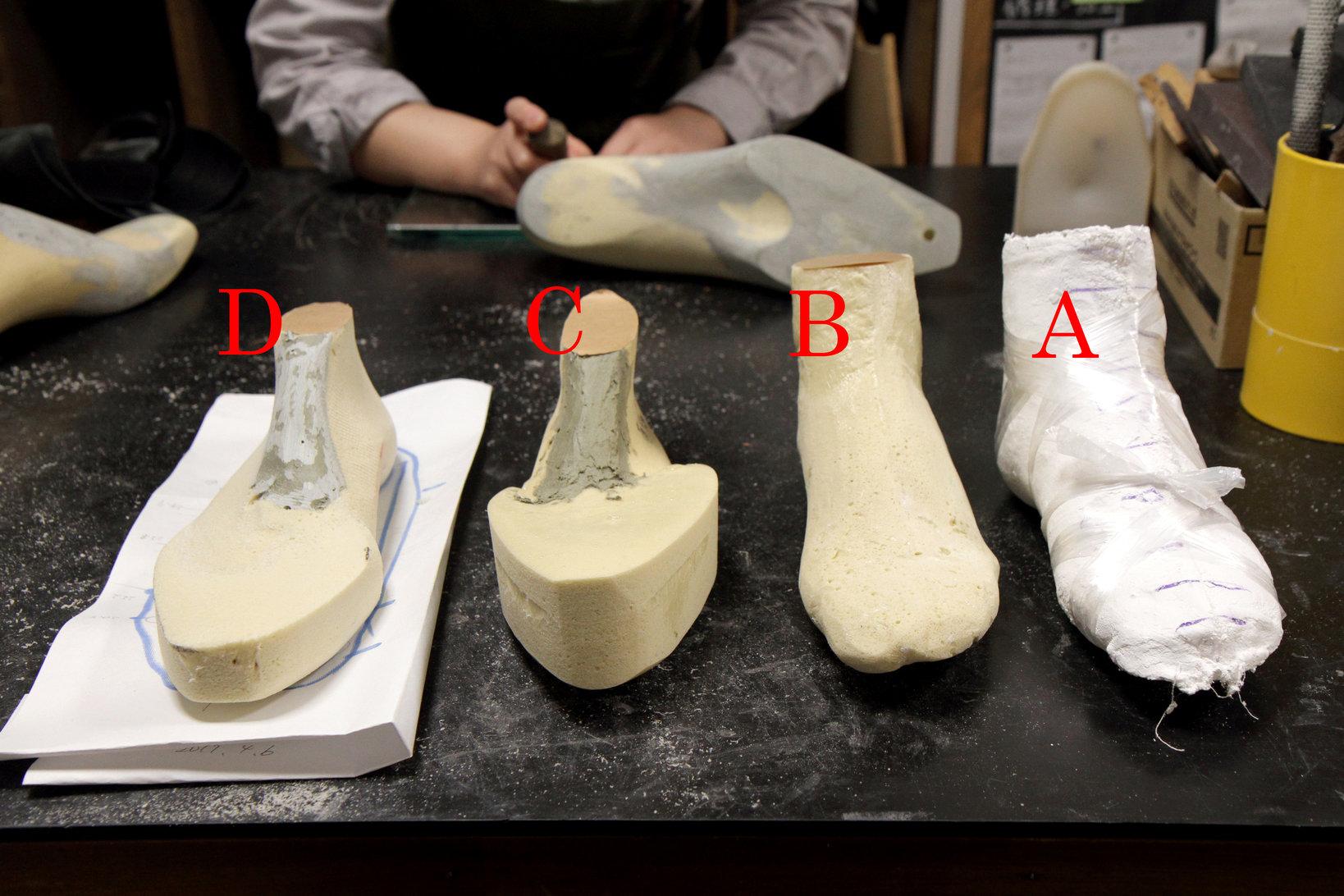 右から、(A)④で出来た石膏ギプス、(B)石膏ギプスに発泡樹脂を流し込み、型を採ったもの、(C)Bに微調整を加えるため、調整箇所に発泡樹脂を足したもの、(D)微調整を加える作業過程のもの