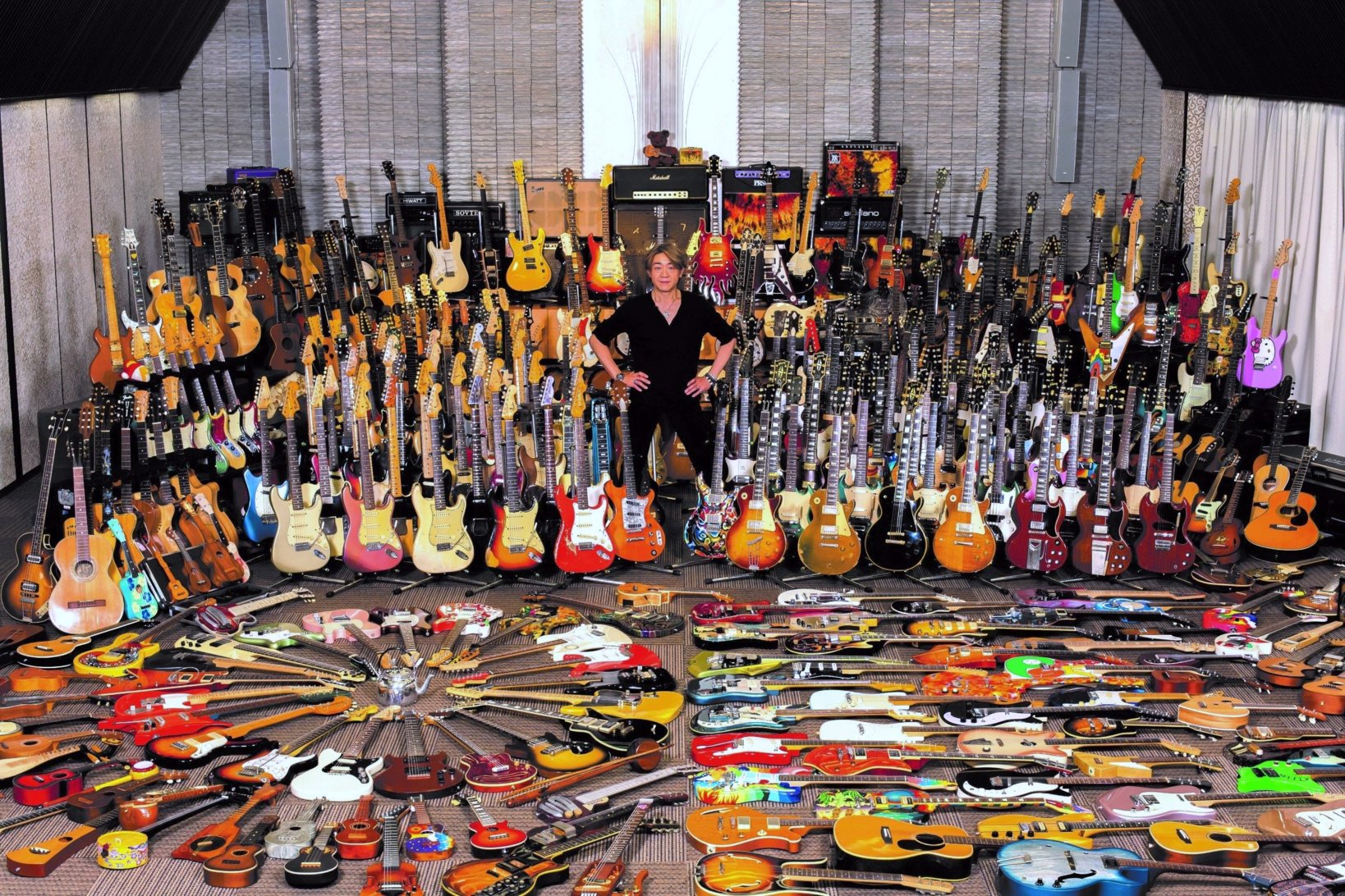 写真集のカバーにもなった迫力満点の一枚。ここに写っている膨大なギターのうち、約100本のギターは、ほかの所有者のもとへ。(撮影:植田山月、提供:リットーミュージック)