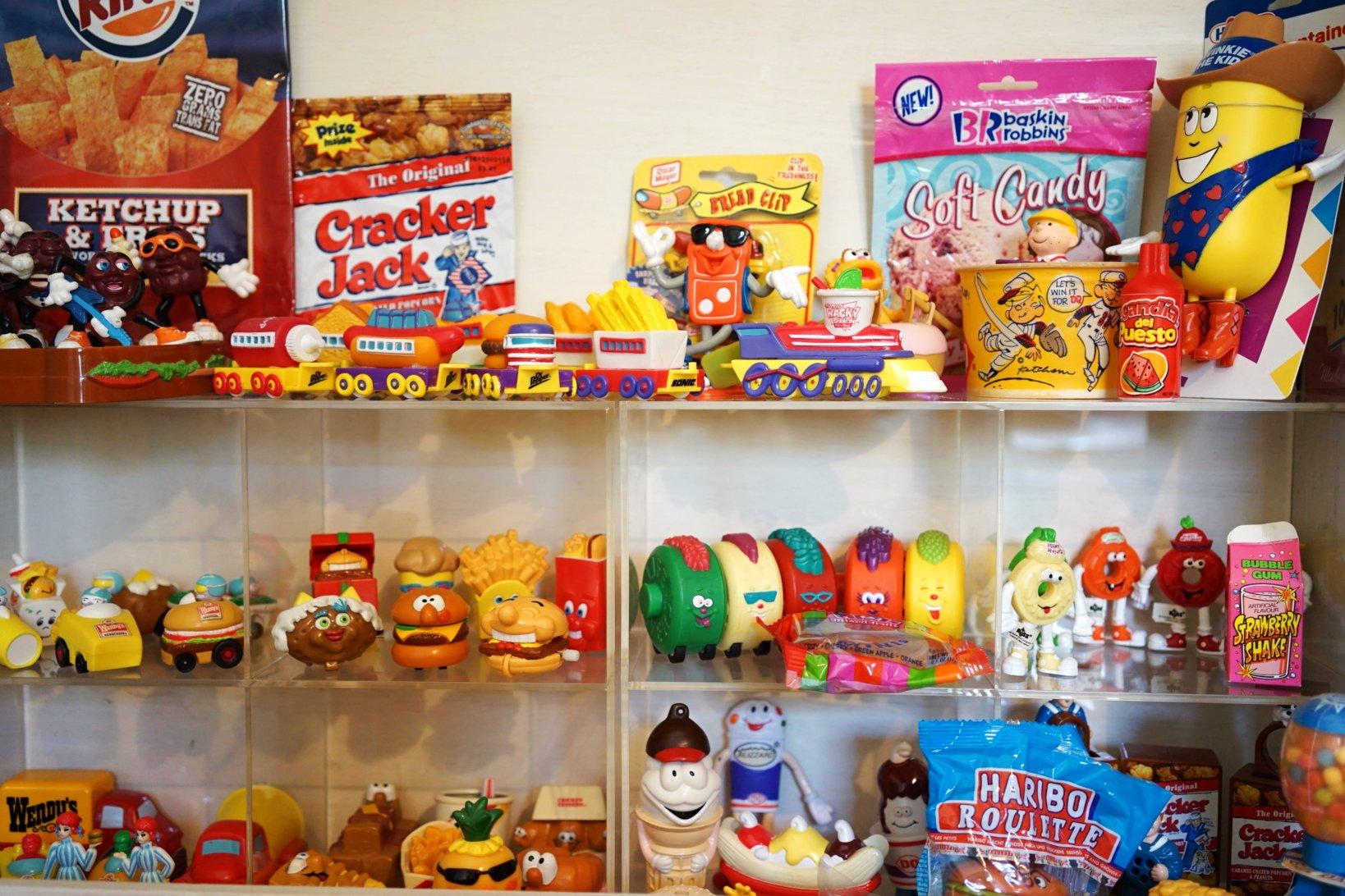 マックけんいちさんのリビングにあるコレクションケース。バーガーチェンのウェンディースやキャンディのブランド・ライフセーバーなどのミールトイが並ぶ。