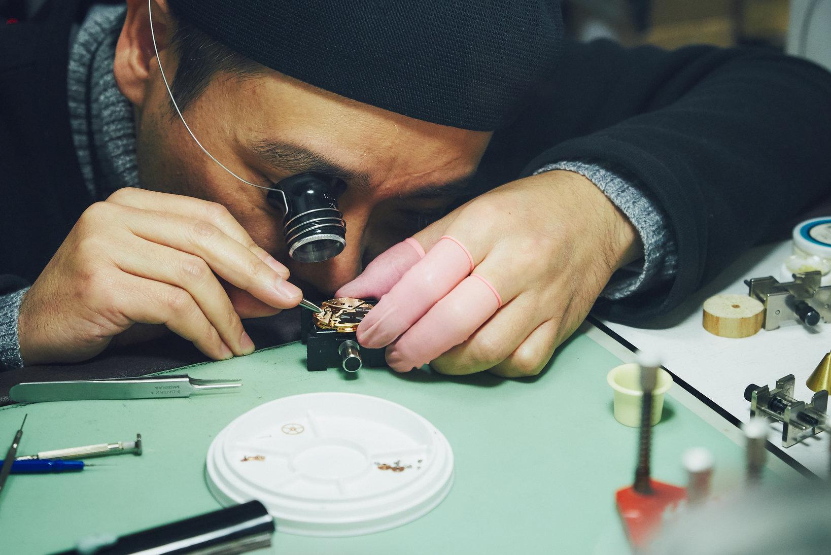 通常は単眼ルーペ(キズミ)を使って作業を行うが、より細かな部分は顕微鏡で確認する。写真は注油しながら組み立てているところ。