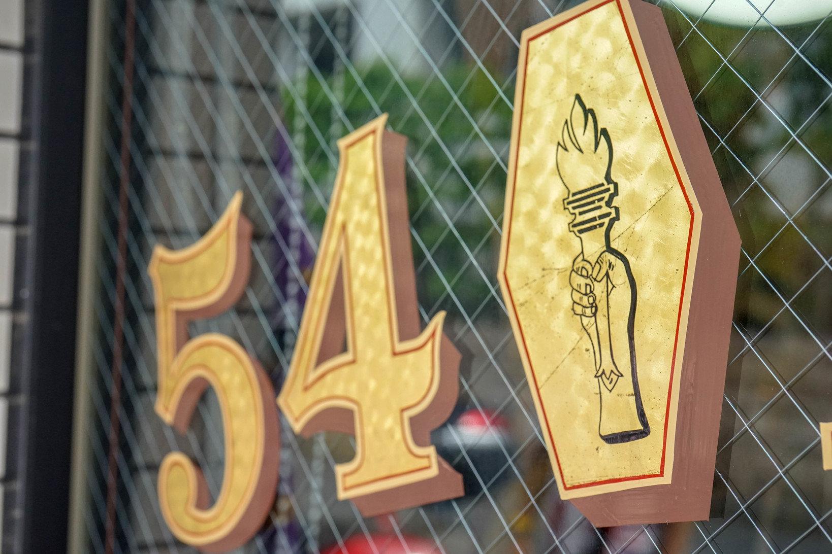 ガラスに貼られているアートワークは、成田さんの友人に施してもらったもの 。金箔でをペタペタと貼り付けてコーティングする手法で作られており、50sのテイストが表現されている。これができる職人さんは少なくなっているそう。