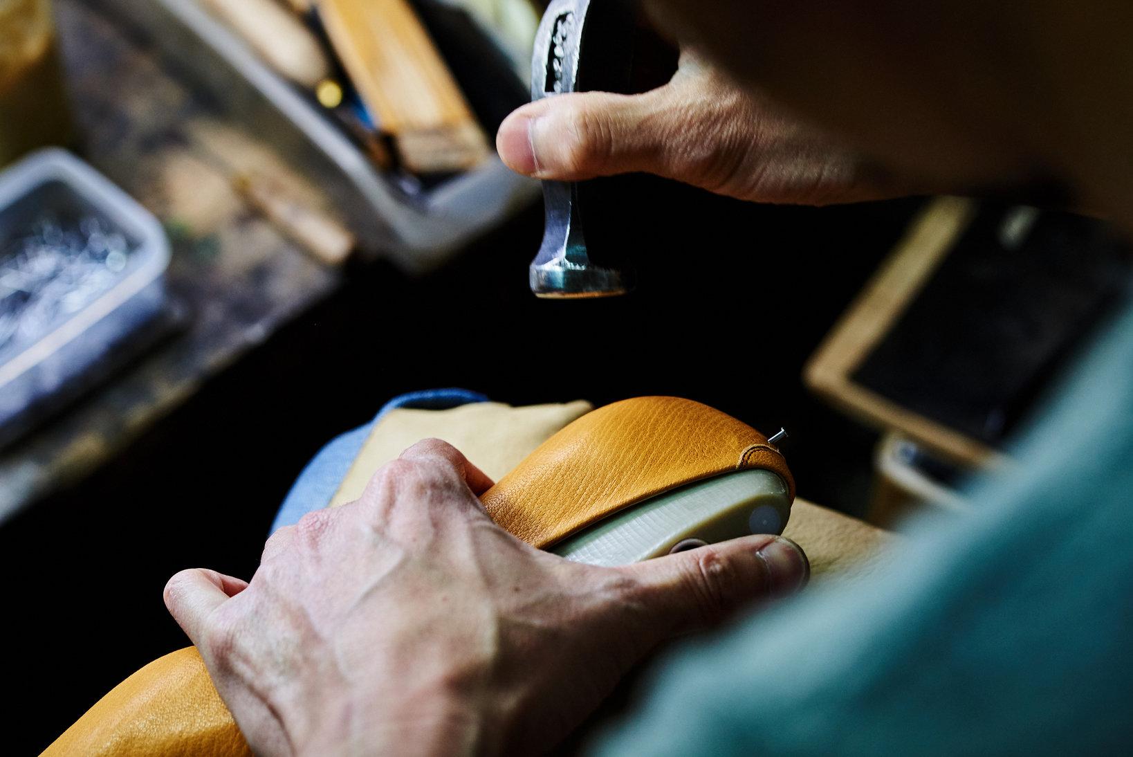 アッパーを木型に吊り込むのも、このように当然手作業。革の特性を確かめながら、トンカチを用いて丁寧に沿わせてゆく。