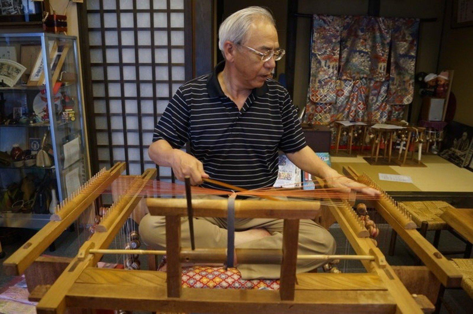 高台に座り糸を組み合わせて紐を作っていく。組紐は地方によって作り方が異なる