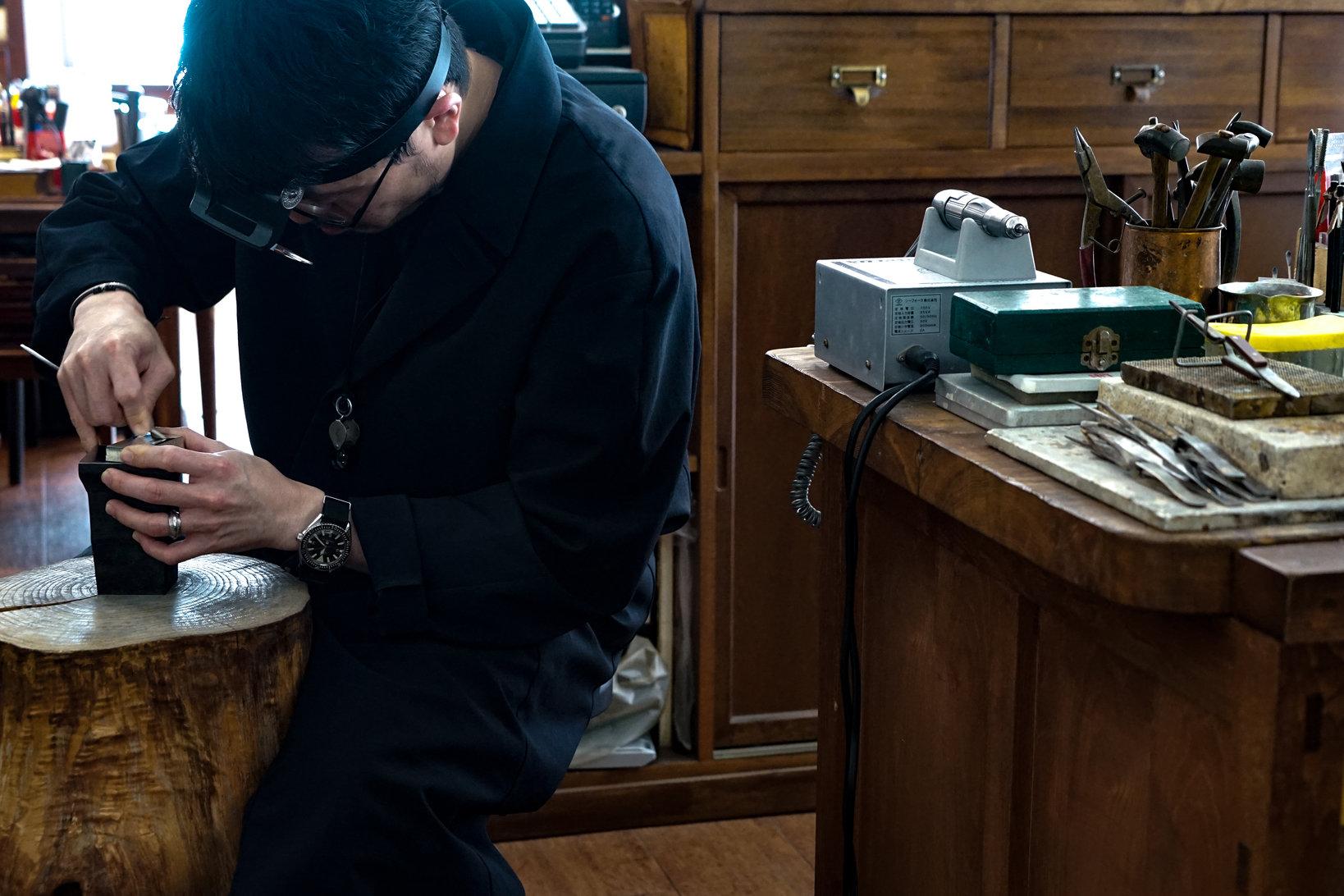 ユニフォームはエプロンではなく全身を包み込むワークコート。ジュエリー製作の現場では、粉塵やオイルなどにまみれて意外と汚れる。フランスのメゾンで働く職人をイメージしたこのコートは吾郎さんの代名詞でもある。