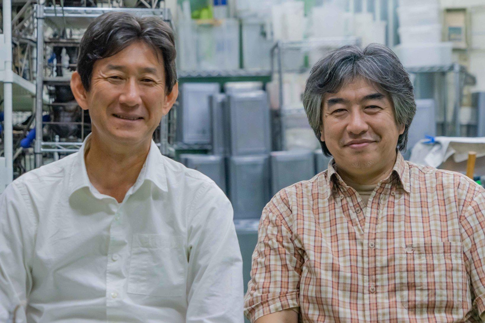 """左:山﨑進一さん。企画会社Y-BOX代表。江崎グリコに21年、バンダイに16年勤務。『アーモンドクラッシュポッキー』や『タイムスリップグリコ』のヒット商品の開発、『ベルばらの大人向け化粧品』『ガンダムカフェ』などの新規事業創出に携わり、定年退職を機に起業、企画会社Y-BOXを立ち上げた。アナログレコードとクワガタをこよなく愛する趣味人でもある。  右:宮澤博一さん。1963年東京生まれ。高校卒業後、洋食のコックの道に進む。家庭の事情で家業を継ぐが、ほどなく古物商に転身。アンティーク玩具店を経営する傍ら、いきなり独学で原型製作を始める。2007年、その原型を元にソフビを製造する会社「シカルナ・工房」を設立。何事も""""出来るようになるまでやり続ける""""性格により、塗装、成型技術を会得した。家庭では、娘たちの高校時代に""""冷凍食品を一切使わない弁当""""を作り続けた父親でもある。"""